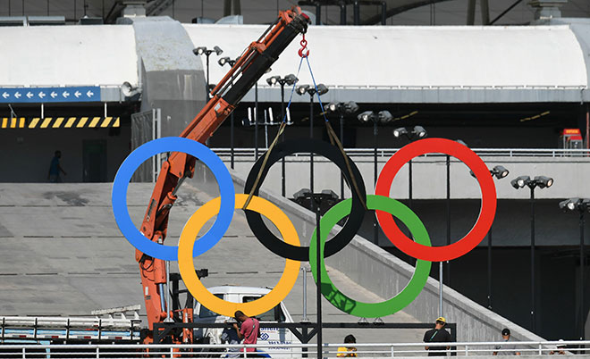 Workers set olympic rings outside the Maracana stadium in Rio de Janeiro on August 5, 2016, ahead of the Rio 2016 Olympic Games' opening ceremony. (AFP)