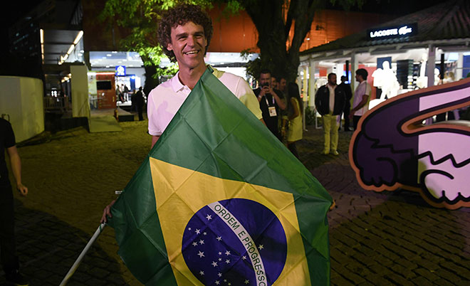 "Brazilian former tennis player Gustavo Kuerten holds the national flag at the ""Club France"" in Rio de Janeiro on August 4, 2016, ahead of the Rio 2016 Olympic Games. (AFP)"