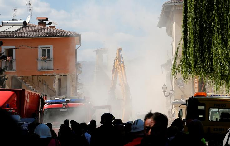 Dust is seen coming out from falling rubble following an aftershock in Amatrice, central Italy. REUTERS