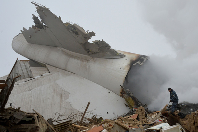 A police officer works at the crash site of a Turkish cargo plane in the village of Dacha-Suu outside Bishkek. (AFP)