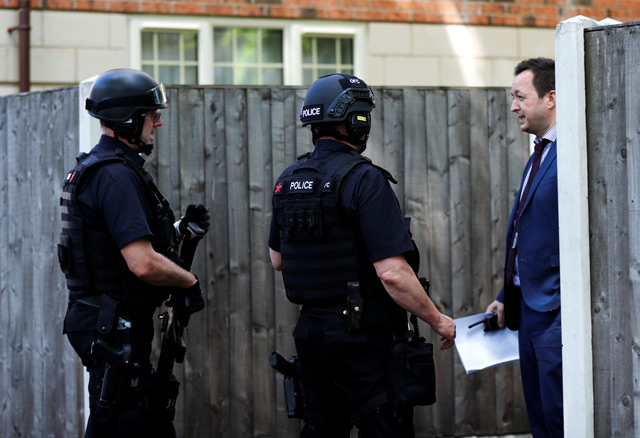 Armed and plain clothes police officers stand outside a residential property near to where a man was arrested in the Chorlton area of Manchester. (Reuters)