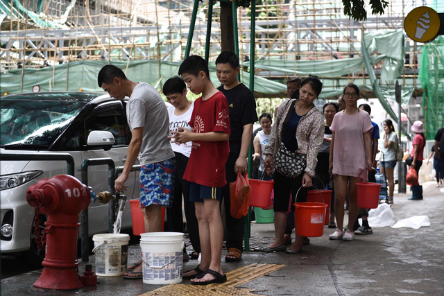 Residents queue up to collect water from a fire hydrant in Macau. (AFP)