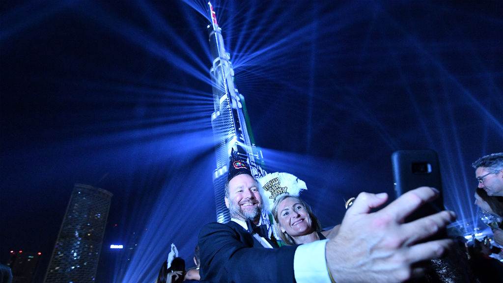 A picture taken on December 31, 2017, shows people posing for a selfie during a laser show at Burj Khalifa, the tallest tower in the world, to mark the New Year's eve celebrations in Dubai. (AFP)