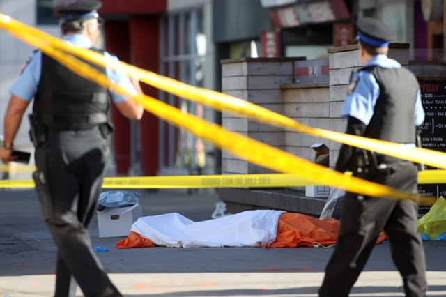 Police officers stand near one of the bodies on the street after a truck drove up on the curb and hit several pedestrians in Toronto. (AFP)