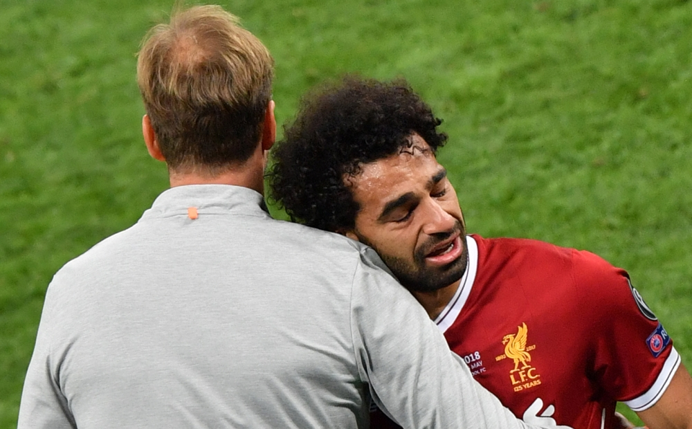 Mohamed Salah (R) is comforted by Liverpool's German manager Jurgen Klopp as he leaves the pitch after injury during the UEFA Champions League final football match between Liverpool and Real Madrid at the Olympic Stadium in Kiev, Ukraine. (AFP)