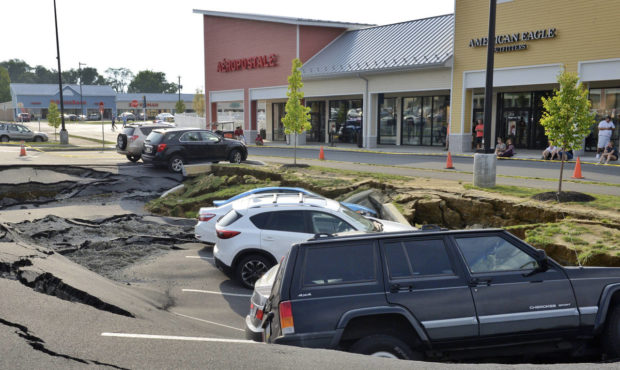 Vehicles sit at the bottom of a sinkhole that opened Friday, Aug. 10, 2018, in a parking lot at Tanger Outlets shopping center in Lancaster, Pa. (AP)
