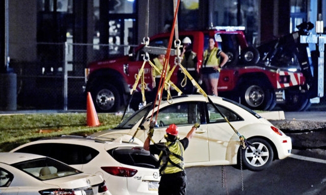 A crane is used to lift vehicles from a sinkhole at Tanger Outlets in Lancaster Pa., shortly after midnight Saturday. (AP)
