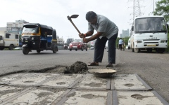 الصورة: Indian man fills potholes out of love for dead son