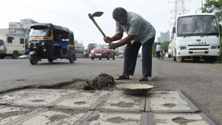 الصورة: Indian man fills potholes out of love for dead son