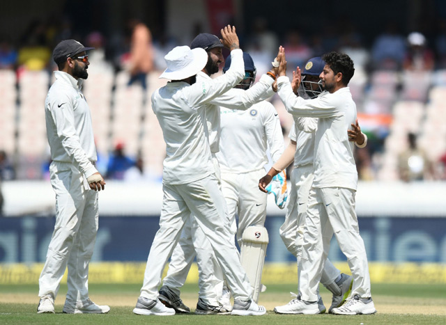 Indian cricket captain Virat Kohli (L) looks on as Kuldeep Yadav (R) celebrates with teammates after the dismissal of West Indies cricketer Sunil Ambris during the first day's play of the second Test cricket match between India and West Indies at the Rajiv Gandhi International Cricket Stadium in Hyderabad. (AFP)