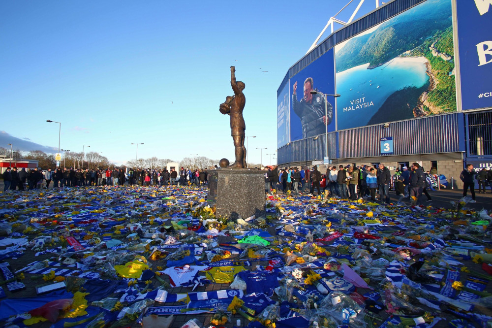 A display of Cardiff City scarves and jerseys, flowers, messages and other tributes to the football club's new signing Emiliano Sala, whose flight disappeared from radar over the English Channel north of Guernsey, is pictured outside the Cardiff City Stadium in Cardiff, south Wales before the English Premier League football match between between Cardiff City and Bournemouth at Cardiff City Stadium in Cardiff, south Wales. (AFP)
