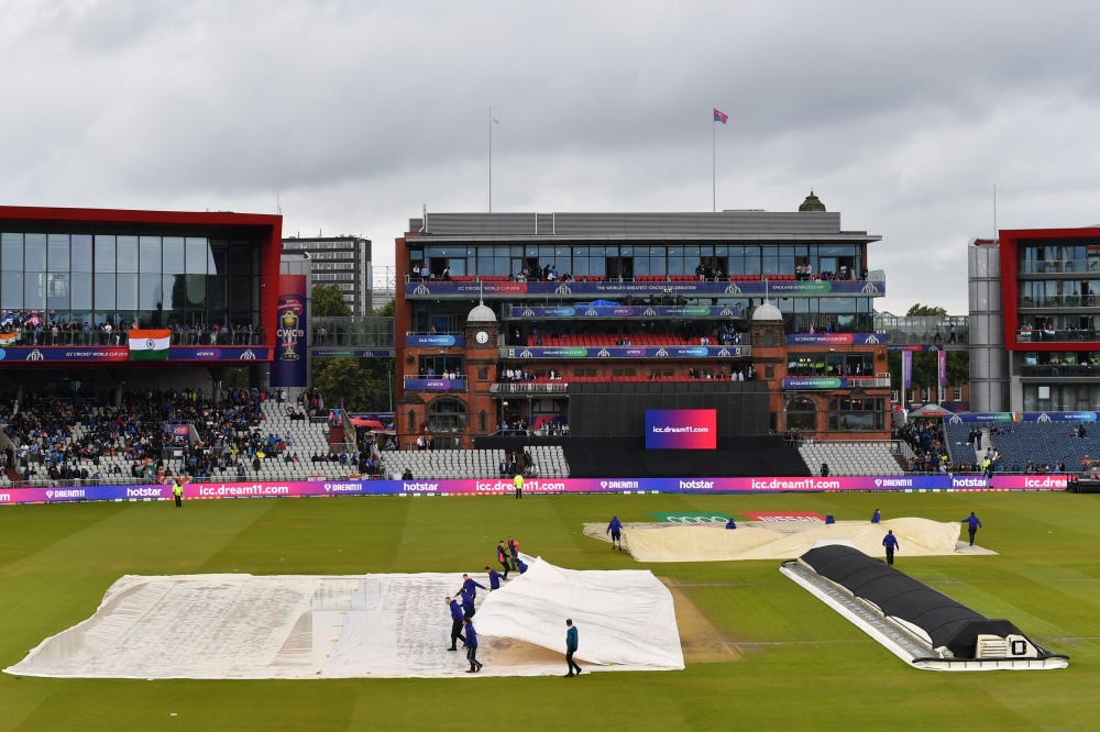 Groundstaff start to remove the covers as the rain stops during the 2019 Cricket World Cup first semi-final between India and New Zealand at Old Trafford in Manchester, northwest England. (AFP)