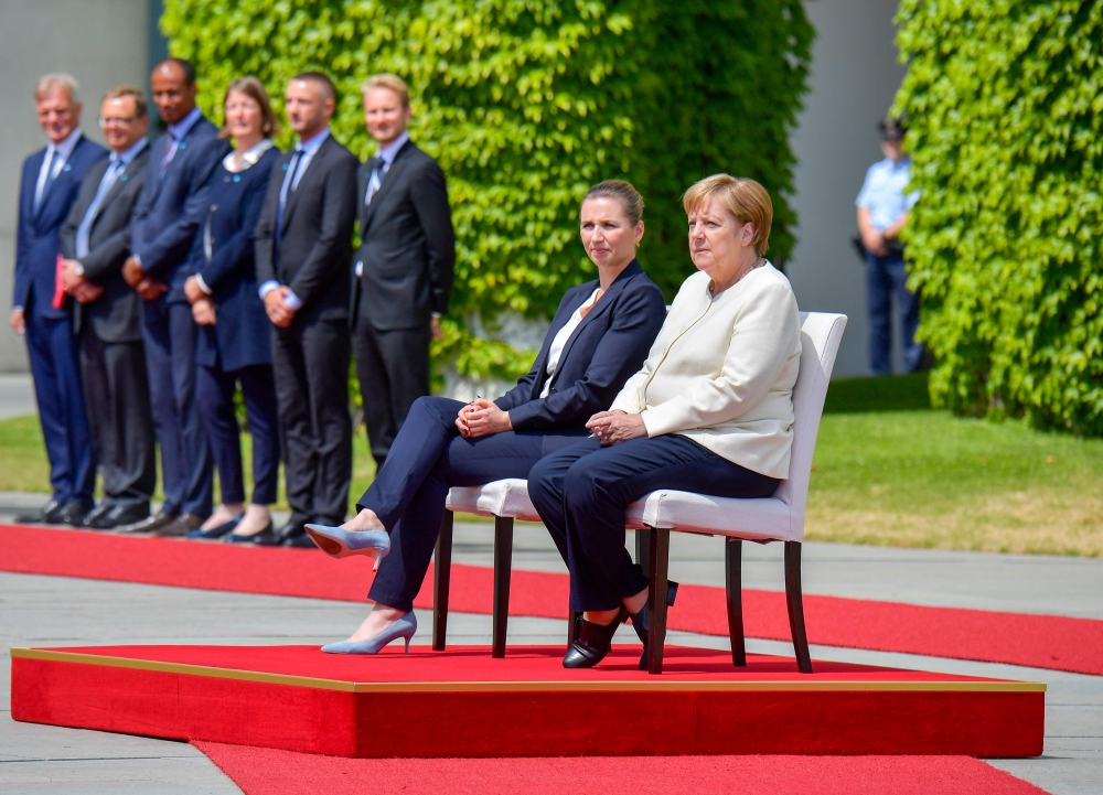 Angela Merkel (R) and Denmark's Prime Minister Mette Frederiksen sit as they listen to the national anthems during a welcoming ceremony with military honours on July 11, 2019 in the courtyard of the Chancellery in Berlin. (AFP)